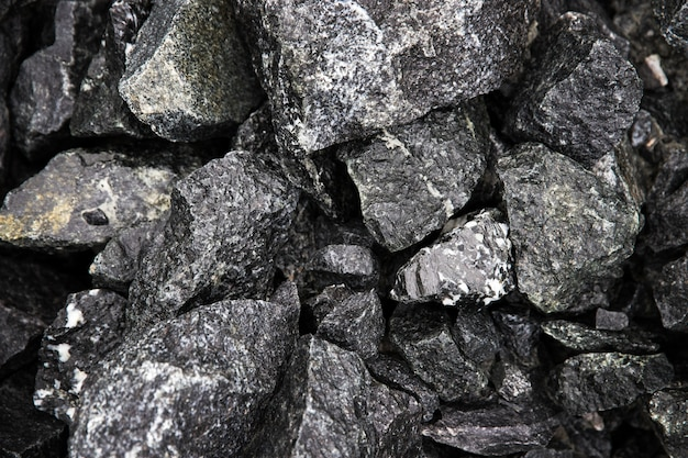 Natte natuurlijke zwarte fragmenten van stenen met afgewisselde knikkers, bovenaanzicht