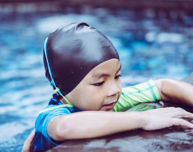 Natte pak aziatische jongen met duikbril is zwemmen in een zwembad