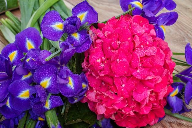 Natte roze hortensia en violette irisbloemen op houten bank