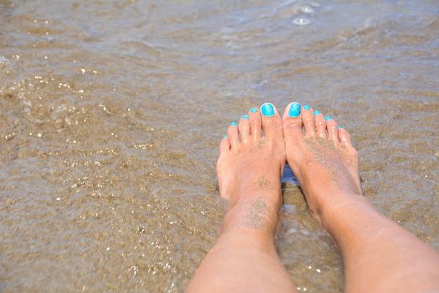 Natte voeten aan de oever van het strand