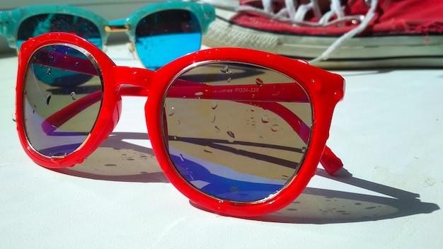 Natte zonnebril en rode sneakers