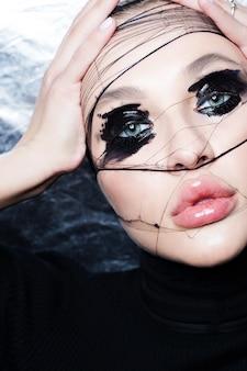 Natte zwarte make-up voor de ogen. creatief schoonheidsportret van een meisje met bergkristallen en gesmeerde lippenstift.