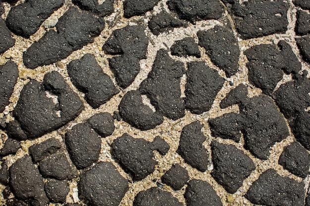 Natte zwarte steen en zand als achtergrond.