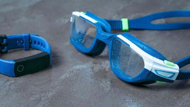 Natte zwembril en fitnessarmband op een stenen ondergrond