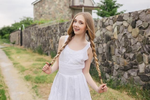 Natuur, architectuur, mensen, mode, natuurlijk concept - modeportret van mooi meisje in boho-stijl in de buurt van scandinavisch huis, huis gemaakt van graniet, stro. meisje in het land.