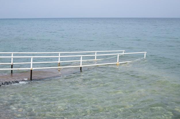 Natuur. de horizon is de lucht en de zee, een gepland ponton. ingang vanaf het strand in het water