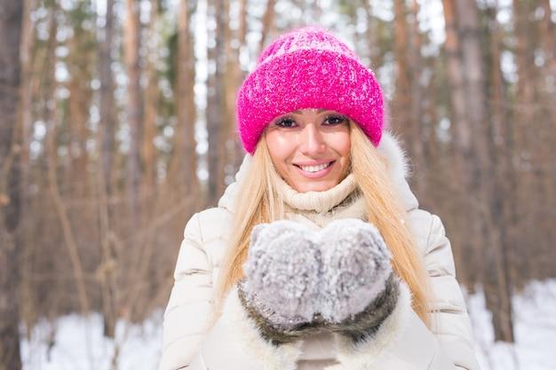 Natuur en mensen concept - close-up portret van aantrekkelijke vrouw gekleed in roze hoed in winter park