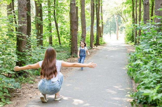 Natuur, familie, mensen concept - schattig klein kind meisje en jonge vrouw in een prachtig bos. dochter loopt naar moeder.
