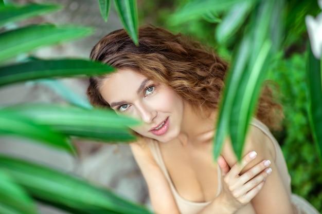 Natuur. jonge vrouw die zich dichtbij de plant bevindt en mooi kijkt