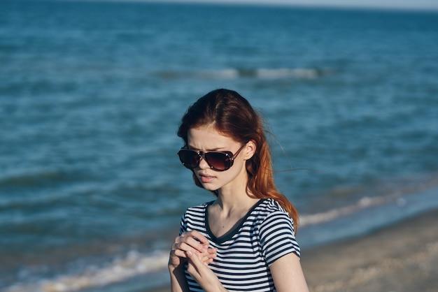 Natuur landschap vrouw in de buurt van de zee op het strand in zonnebril