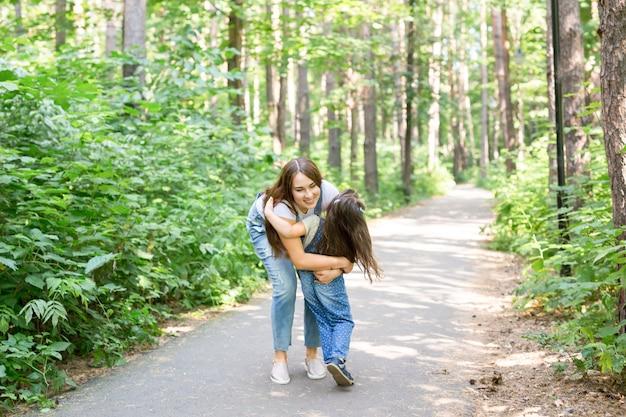 Natuur, moederschap en kind concept - gelukkige moeder en dochtertje hebben plezier in groen park