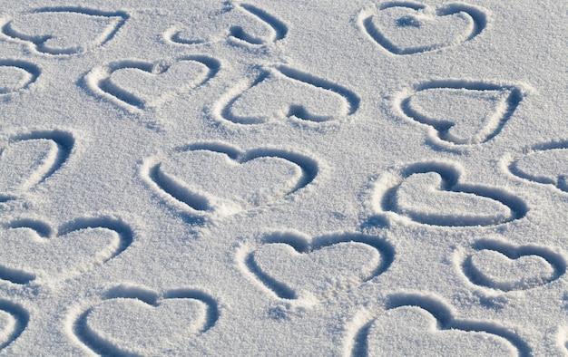 Natuur na sneeuwval en op het oppervlak van de sneeuw, getekend in het winterseizoen, het hart op de sneeuw, het hart is getekend als een symbool van liefde