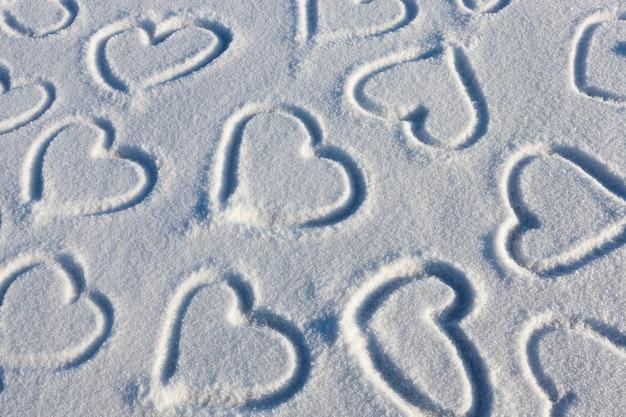 Natuur na sneeuwval en op het oppervlak van de sneeuw, wordt het hart getekend als een symbool van liefde, getekend in het winterseizoen, het hart op de sneeuw