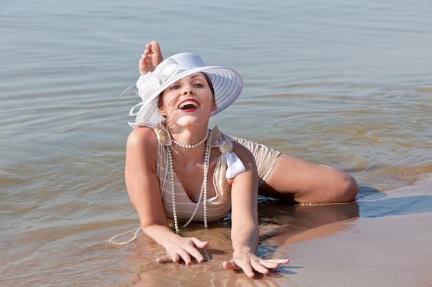 Natuur, schoonheid, jeugd en gezonde levensstijl concept. vrouw in een gestreept retro badpak met een witte paraplu en witte hoed tegen de zee