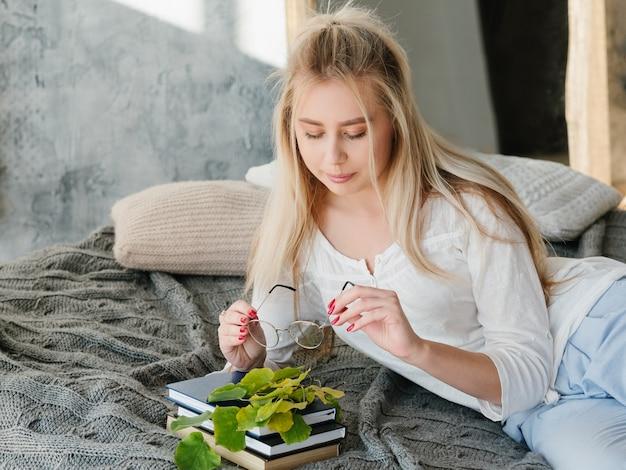 Natuur studie concept. bioloog hobby. portret van vrouwelijke wetenschapper die rust op bed met boeken heeft.