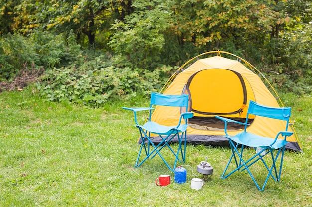 Natuur, toerisme en avontuur concept - oranje tent in bos met gezellige sfeer.