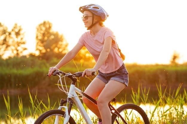 Natuur. vrolijke jonge vrouw fietsen op de promenade langs de rivier en de weide. geïnspireerd door de omgeven natuur, zomerse sfeer. warme zonneschijnkleuren. sport, activiteit, wellness, plezierconcept.