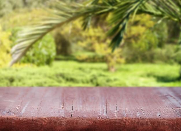 Natuurachtergrond met houten basis en uitzicht op de palmbladeren en planten