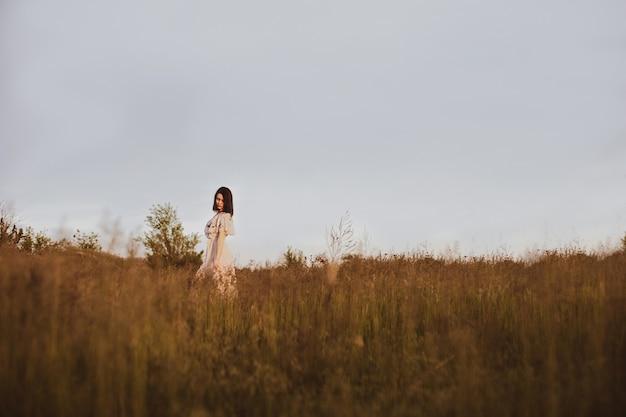 Natuurlandschap met lang wild gras en wandelende romantische vrouw bij warme zonsondergang, zomerdorpsvrije tijd