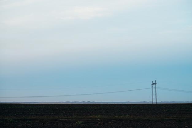 Natuurlandschap met silhouetten van hoogspanningsleidingen in veld
