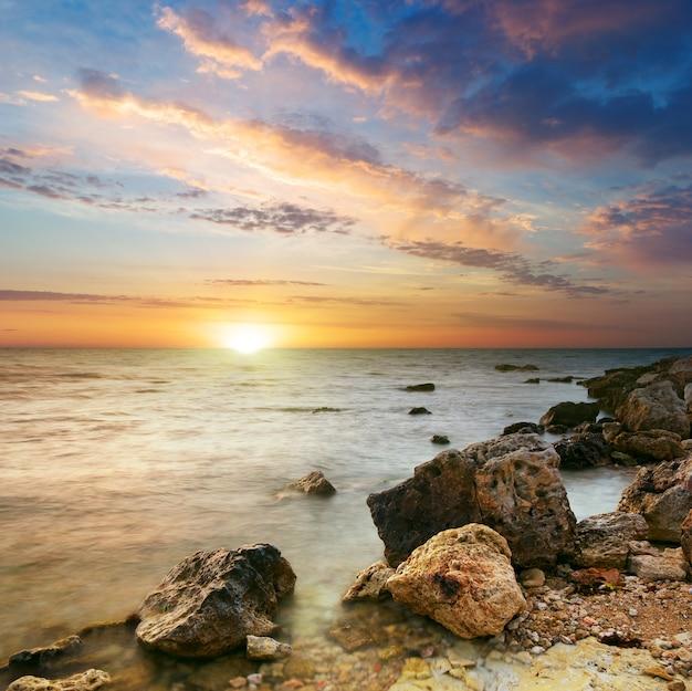 Natuurlandschap van zee en rots bij de zonsondergang.
