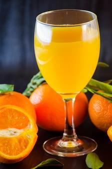 Natuurlijk biologisch vers mandarijnensap in een glas op een donkere achtergrond