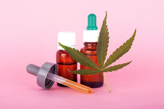Natuurlijk cannabisgeneesmiddel, marihuanaolie-extract op roze achtergrond.