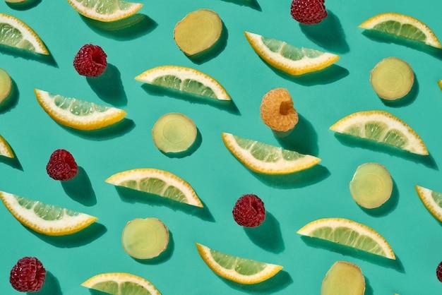 Natuurlijk fruitpatroon met rijpe frambozen een plakjes citroen en gember op een blauwe achtergrond. concept van behandeling van verkoudheid met natuurlijke ingrediënten. bovenaanzicht.