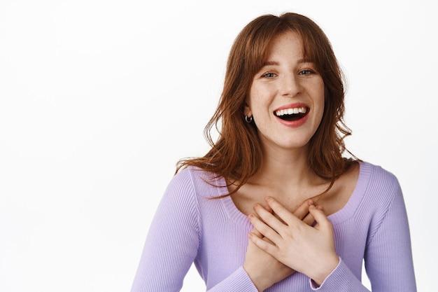Natuurlijk gelukkig meisje, hand in hand op het hart, glimlachend witte tanden, oprecht lachend, kijkend naar iets grappigs en hilarisch, staand in paarse blouse op wit