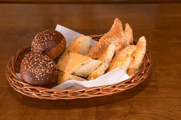 Natuurlijk graan landelijk brood met kruiden, kruiden en sesamzaadjes in een rieten mand