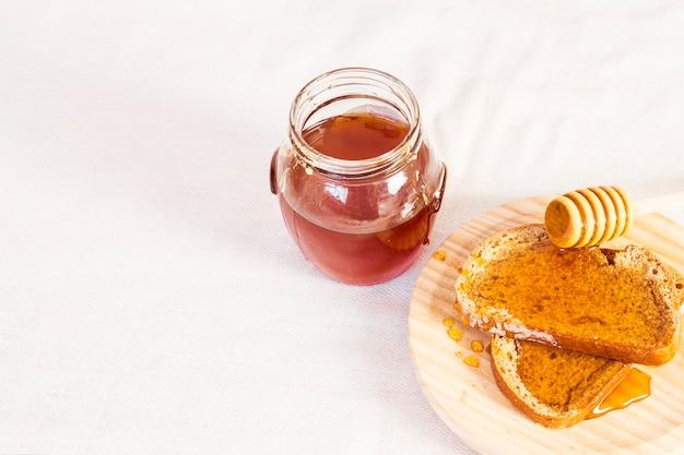 Natuurlijk honing en brood voor gezond ontbijt dat op witte oppervlakte wordt geïsoleerd