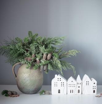 Natuurlijk kerstboeket in oude keramische kruik met witte huizen op grijze achtergrondmuur