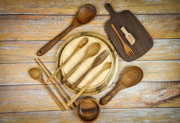 Natuurlijk keukengereedschap houtproducten / keukengerei achtergrond met lepel vork eetstokjes kom plaat snijplank object, bovenaanzicht op de tafel gebruiksvoorwerp houten