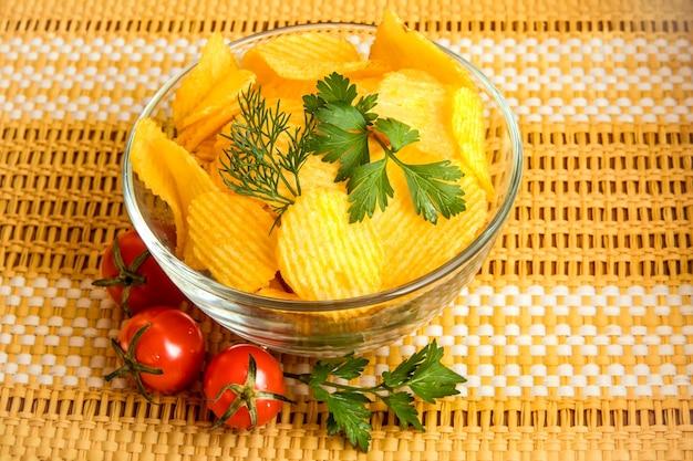 Natuurlijk knapperige aardappelchips in een doorzichtige kom met blaadjes dille en peterselie en drie cherrytomaatjes