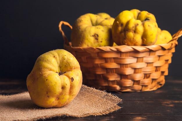 Natuurlijk kweepeerfruit met gebreken in een mand op een juteservet en een donkere houten achtergrond.