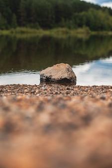 Natuurlijk landschap van het meer, hoge definitie, de beweging van golven tegen de achtergrond van het bos. de weerspiegeling van wolken op de rimpelingen van water. op de voorgrond is een grote steen