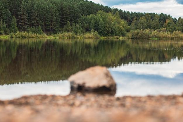 Natuurlijk landschap van het meer, hoge resolutie. weerspiegeling van wolken op waterrimpelingen. de oever van het meer is gemaakt van kleine stenen. op de voorgrond is een grote steen onscherp