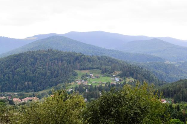 Natuurlijk landschap van hooglanden. een klein dorpje tussen weilanden, bergen en heuvels.