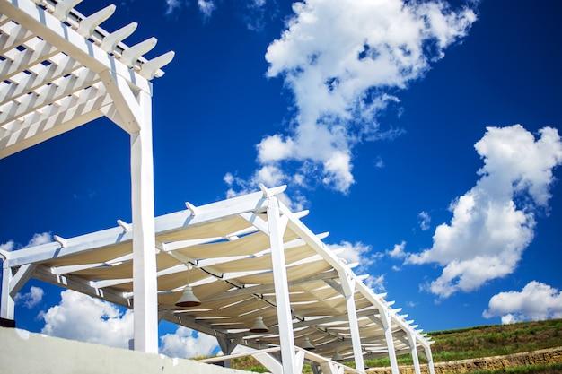 Natuurlijk licht. zonnebaden. houten niveaus tegen de lucht. houten strandluifel.