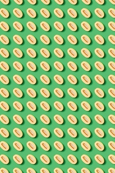 Natuurlijk organisch fruitpatroon van gesneden helften van watermeloenen op een groene muur. bovenaanzicht boven geometrische lijnen.