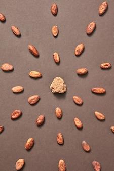Natuurlijk organisch patroon van cacaomassa in het midden van cacaobonen op een bruine achtergrond. plat leggen. droge ingrediënten voor het maken van donkere chocolade.