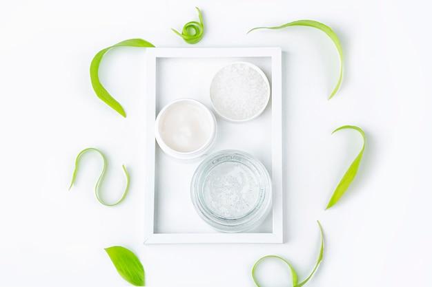 Natuurlijk organisch zelfgemaakt cosmetica concept. huidverzorging, remedie en schoonheidsproducten: containers met room en serum onder groene bladeren op witte achtergrond