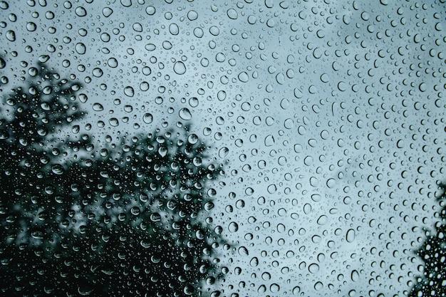 Natuurlijk patroon van waterdalingen op vensterglas tijdens regenachtig weer