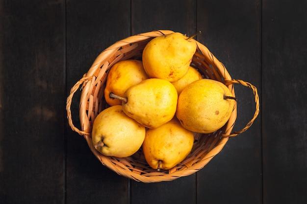 Natuurlijk perenfruit met gebreken in mand op donkere houten achtergrond.