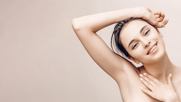 Natuurlijk schoonheidsportret van vrouwelijk gezicht en lichaam met perfecte huid. deodorant reclame en haar epileren concept