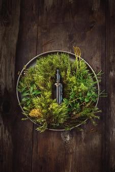 Natuurlijk serum in een fles voor huidverzorging op een green van verse planten