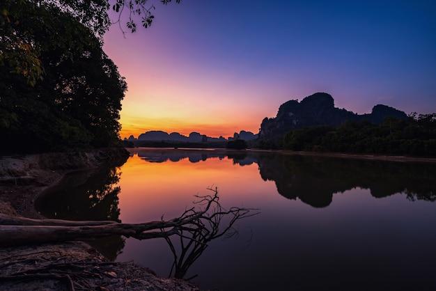 Natuurlijk uitzicht op het prachtige meer en kalkstenen karstgebergte bij dageraad met schemerhemel en reflectie op water, nong thale, krabi, thailand. beroemde reisbestemming in het zuiden van thailand.