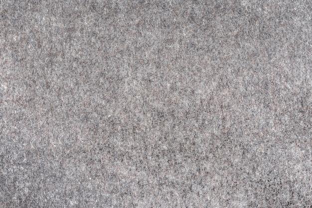 Natuurlijk vilt van grijze kleur als abstracte achtergrond de textuur en het patroon van het materiaal