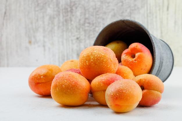 Natuurlijke abrikozen in een mini emmer. zijaanzicht.