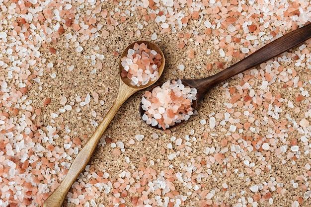 Natuurlijke achtergrond voor spa. grote kristallen van roze himalayazout opgestapeld met een dia in houten lepels.